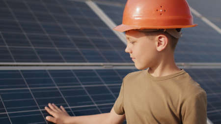 Little boy in a protective helmet at a solar power plant. The concept of children and green energetics. Children for clean energy. Shooting at a solar power plant. Ecological farm. Solar power station Standard-Bild