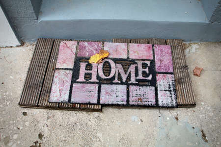 welcome mat: welcome - mat in front of the house with the word Home Stock Photo