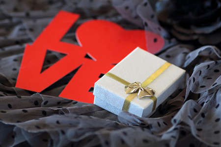 Romantic background with a gift and a red word love