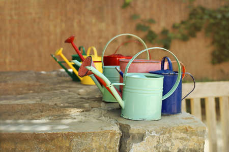 Colored watering cans on a stone wall in the garden Standard-Bild