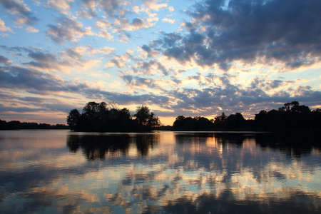 The sunset over the lake, the reflection of the clouds in the lake Standard-Bild