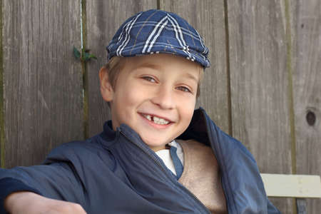 Cute smiling boy in his hat and blue coat, outdoor Standard-Bild