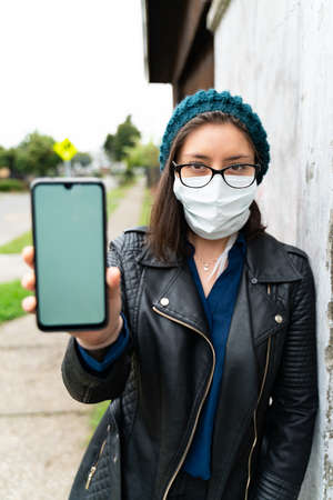 woman with mask shows the screen of her cell phone