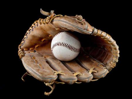 guante de beisbol: Una pelota de béisbol en un guante con fondo negro  Foto de archivo