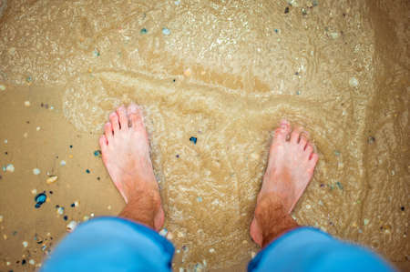 men s feet: The guy looks at his feet in the sea.
