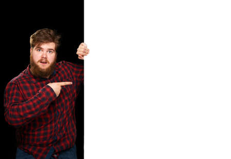 nice guy: Nice guy pointing in surprise at a white wall on a black background Stock Photo