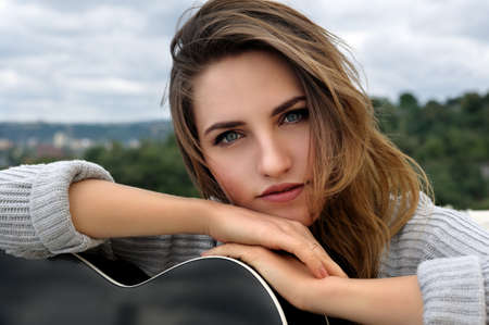 leaned: Portrait of a beautiful girl who leaned on the guitar