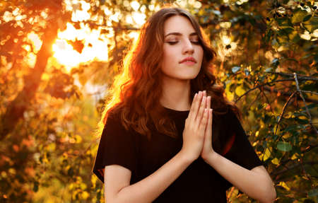 The girl prays in nature eyes closed Stock Photo