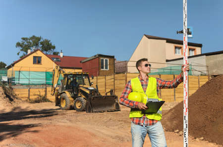 Foreman on construction background with a clipboard in his hands