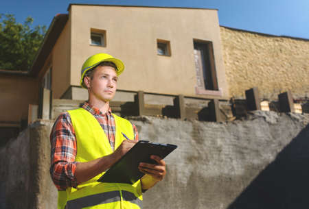 foreman: Foreman on construction background with a clipboard in his hands