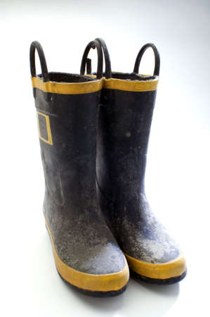 a pair of dirty rubber boots on white Stock Photo
