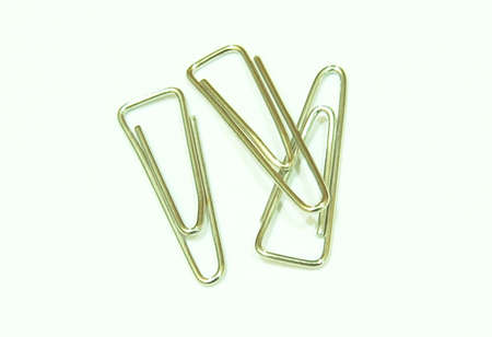 trigonal: Metal paper clips on white background