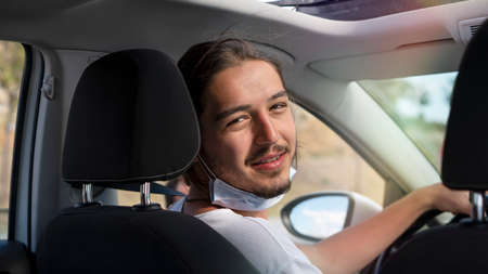 Young handsome man in mask sitting on the front passenger seat inside of a car smiles looking at camera.