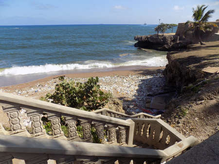 excrement: steps leading down to a beach with trash