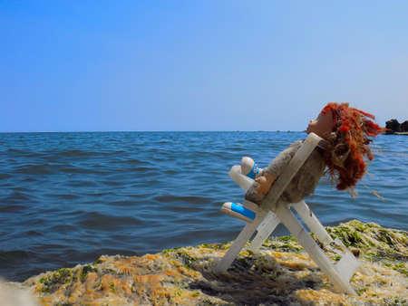 una muñeca sucia con el pelo rojo mirando el mar sentado en una silla rota.