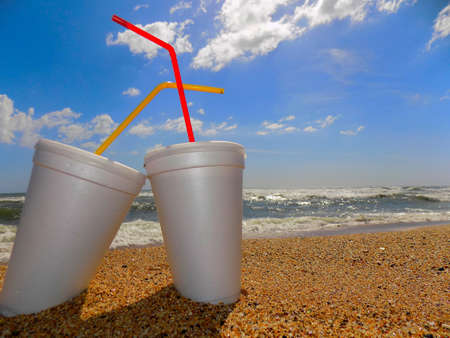 Two glasses of expanded polystyrene (polystyrene foam), with lids and straws, on the beach, partially buried in the sand. Stock Photo