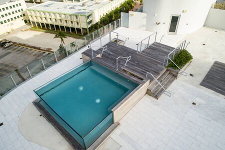 Aerial image of a contemporary rooftop swimming pool made from glass walls Editöryel