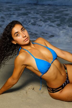 Image of a bikini model posing on the beach lit with flash and softbox Stock Photo