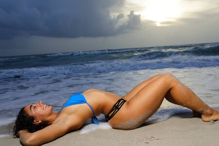 Image of a woman laying in a bikini on the sand lit with off camera flash