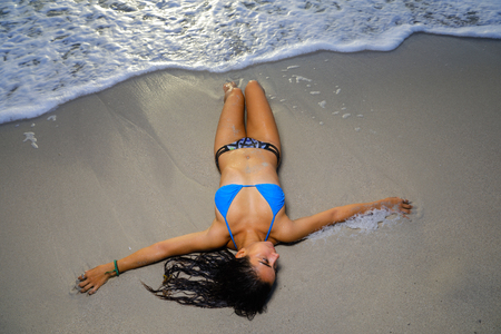 Stock photo of a sexy young bikini model laying on the beach by the waves