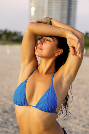 Image of a bikini model posing with her arms above her head on the beach