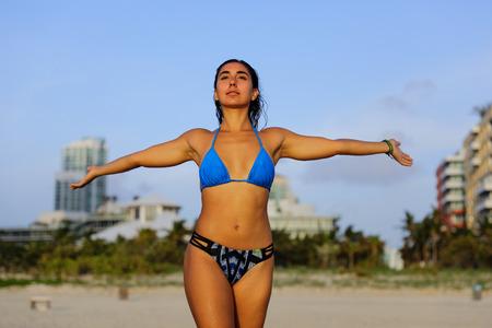 Image of an attractive woman posing on the beach in her bikini