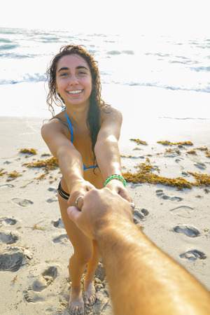 Image of a woman pulling boyfriend by hand into the ocean