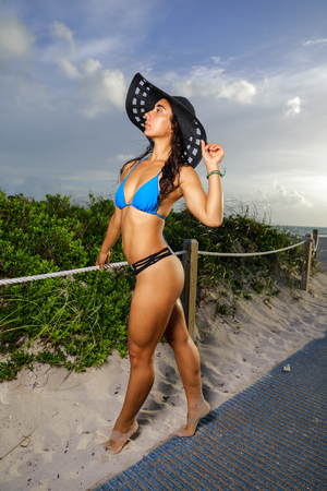 Image of a sexy young bikini model posing on the beach with a hat