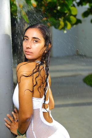 Image of a woman in swimwear taking a shower on the beach Stok Fotoğraf