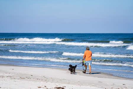 Crescent Beach, FL, USA - December 12, 2020: Man walking his gods on Crescent Beach FL USA
