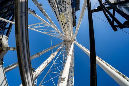 White metal industrial ferris wheel on blue sky Foto de archivo