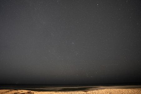 Starry night sky over ocean long exposure photo Foto de archivo