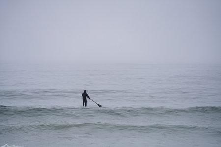 Man paddeleboarding in New Hampshire in the winter Foto de archivo