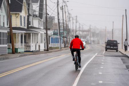 Hampton Beach, NH, USA - December 12, 2020: Man with a red jacket riding a bike in Long Sands Beach Maine