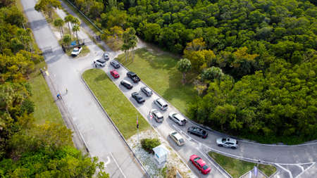 Miami, FL, USA - January 3, 2021: Lines of vehicles waiting to get into Oleta Park which is restricting visitor entrance to social distance Covid 19 Coronavirus pandemic