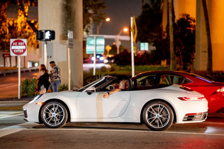 Miami, FL, USA - July 9, 2021: Man in a Porsche sports car waiting at a traffic light in the city Publikacyjne