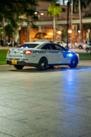 Police car with lights on in the park
