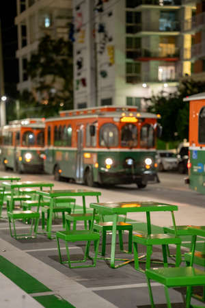 Focus on benches in the city with blurry trolleys in the background Foto de archivo