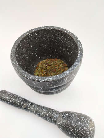grinding oregano with stone mortar