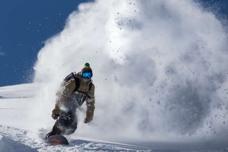 male snowboarder curved and brakes spraying loose deep snow on the freeride slope. Banco de Imagens