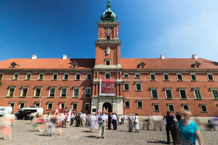 Royal Castle in Warsaw with people standing in front of the building in a summer day, Poland