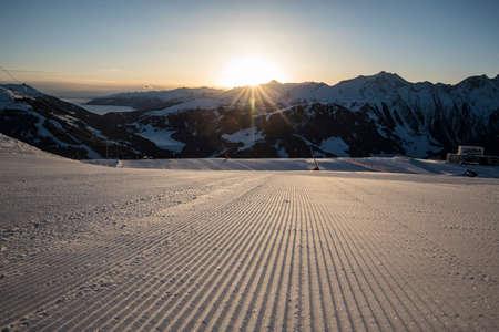Ski tracks on a fresh groomed piste.