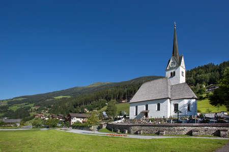 Beautiful church in a mountain landscape on a sunny day in austria. Banco de Imagens