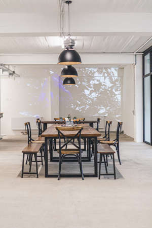 Dining room of a modern office with industrial tables and chairs.
