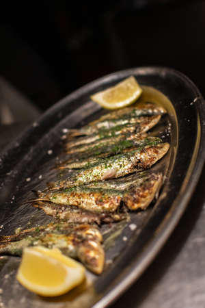Grilled sardines with parsley and lemon ready to be served in a restaurant