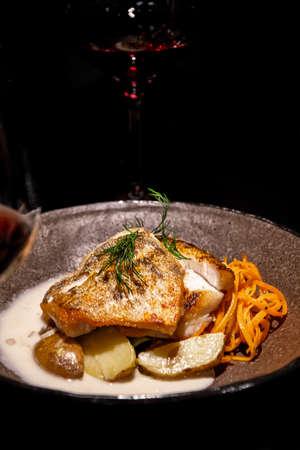 Grilled fish with vegetables as garnishment served elegantly in a restaurant Standard-Bild - 157132752