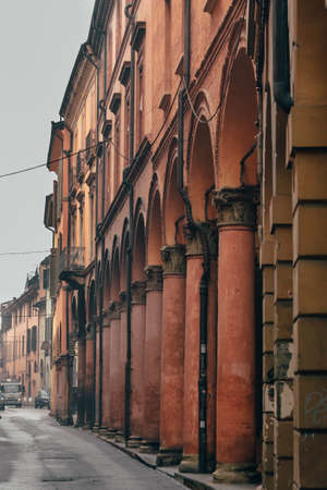 Bologna's streets architecture with red arches and columns