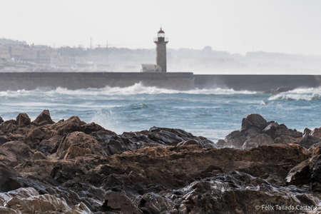Windy and wavy day in Foz, the coast of Porto, Portugal. There is a lighthouse used to guide the ships in ancient times.