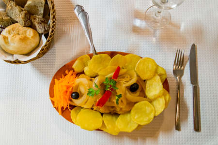 """Traditional and delicious codfish dish called """"Bacalhau a Braga"""". It is served in a restaurant with side laminated potatoes and some vegetables like carrot or olives."""