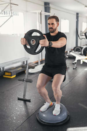 man caucasian handsome and big muscle in sportswear. Young man holding weights during an exercise class in a gym. Healthy sports lifestyle, Fitness concept.Vertical.